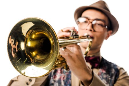 Photo for Selective focus of mixed race male musician in stylish hat and eyeglasses playing on trumpet isolated on white - Royalty Free Image