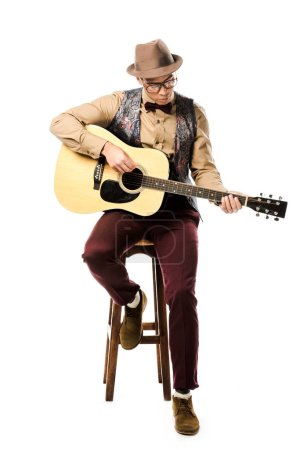 Photo for Focused mixed race male musician in hat and eyeglasses playing on acoustic guitar while sitting on chair isolated on white - Royalty Free Image