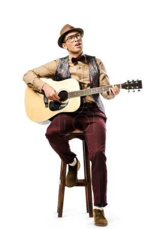 Photo for Smiling mixed race male musician in hat and eyeglasses playing on acoustic guitar while sitting on chair isolated on white - Royalty Free Image