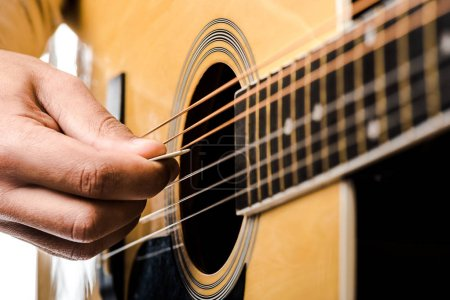 partial view of male musician playing on acoustic guitar isolated on white