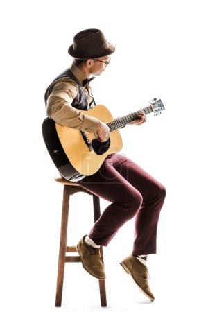 Photo pour Musicien mâle jeune métisse en chapeau et des lunettes, jouant à la guitare acoustique, tandis qu'assis sur la chaise isolé sur blanc - image libre de droit
