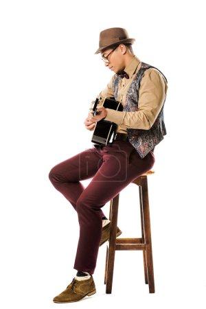 Photo pour Vue latérale du musicien mâle de race mixte en chapeau et des lunettes, jouant à la guitare acoustique, tandis qu'assis sur la chaise isolé sur blanc - image libre de droit