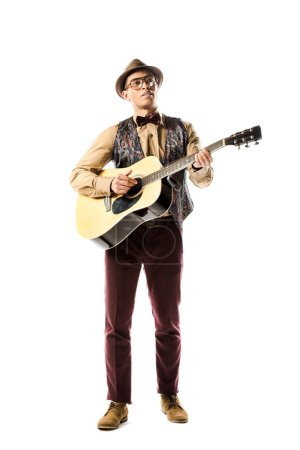 mixed race male musician in hat and eyeglasses playing on acoustic guitar isolated on white