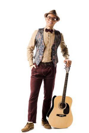 Photo for Happy male musician in hat and eyeglasses posing with acoustic guitar isolated on white - Royalty Free Image