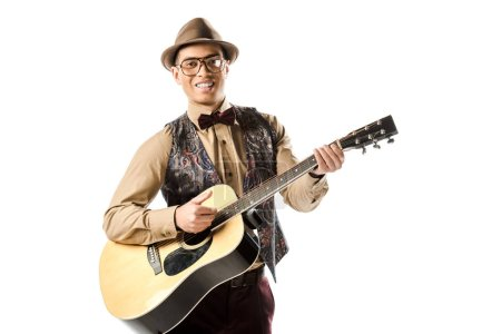 happy mixed race male musician in hat and eyeglasses playing on acoustic guitar isolated on white