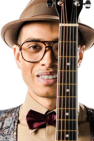 Photo pour Portrait de joyeux musicien mâle dans le chapeau et des lunettes posant avec guitare acoustique isolé sur blanc - image libre de droit
