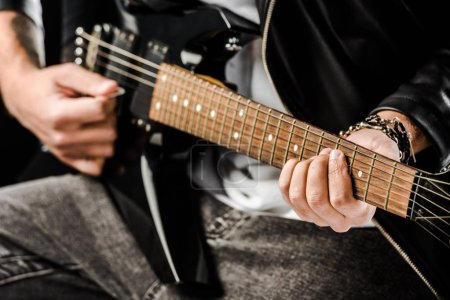 cropped shot of male rock musician in leather jacket playing on electric guitar isolated on white