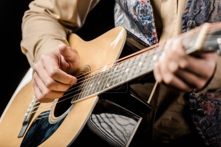 Photo for Cropped image of male musician playing on acoustic guitar isolated on black - Royalty Free Image