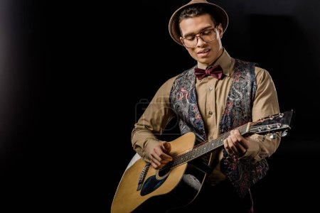 Photo for Handsome male musician in eyeglasses and hat playing on acoustic guitar isolated on black - Royalty Free Image