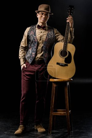 male musician in stylish hat posing with acoustic guitar near chair on black