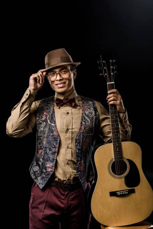 cheerful mixed race male musician in eyeglasses and hat posing with acoustic guitar isolated on black