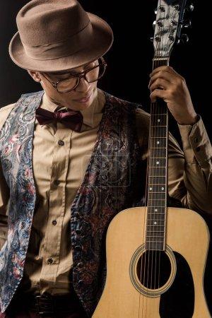 Photo pour Musicien mâle jeune métisse à lunettes et un chapeau posant avec guitare acoustique isolée sur fond noir - image libre de droit