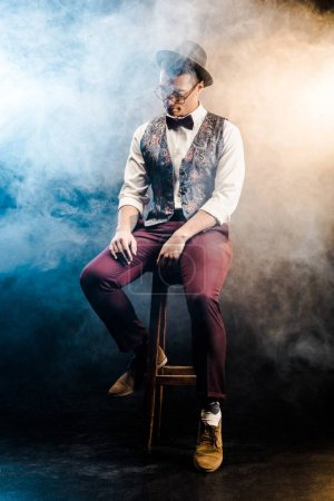 Foto de Hombre joven de raza mixta moda posando en silla en el escenario con iluminación humo y dramática - Imagen libre de derechos