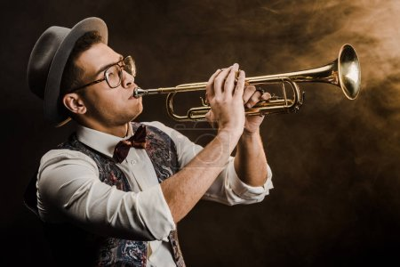 Photo for Young mixed race jazzman in hat and eyeglasses playing on trumpet on stage with dramatic lighting and smoke - Royalty Free Image