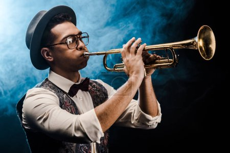Photo pour Musicien mâle en chapeau et lunettes de vue en jouant sur la trompette sur scène avec un éclairage dramatique et fumée - image libre de droit