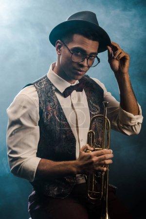 Photo pour Confiant élégant jeune homme au chapeau et des lunettes posant avec trompette sur scène avec un éclairage fumée et dramatique - image libre de droit