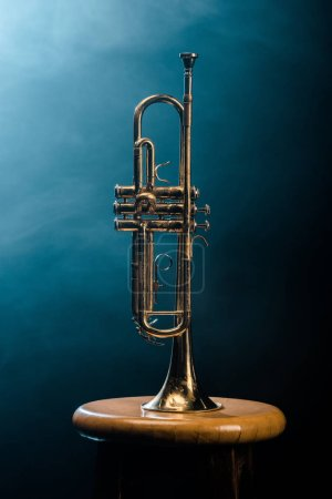 studio shot of trumpet on chair with dramatic lighting background
