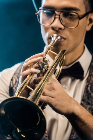 Foto de Enfoque selectivo del jazzman joven jugando en la trompeta en el escenario con iluminación y humo - Imagen libre de derechos