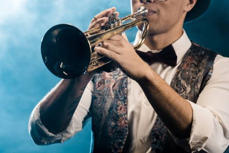 Photo for Partial view of male musician playing on trumpet on stage with dramatic lighting and smoke - Royalty Free Image