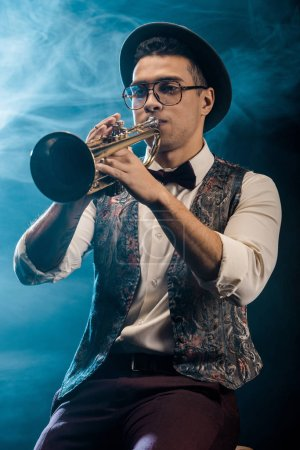 Photo pour Confiant jeune jazzman jouer sur la trompette sur scène avec un éclairage dramatique et la fumée - image libre de droit