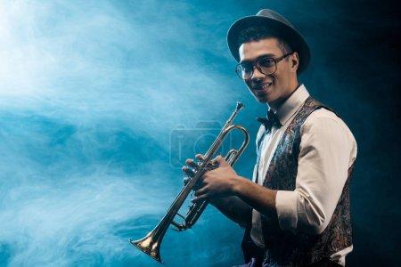 Foto de Músico masculino sonriente posando con trompeta en el escenario con iluminación y humo - Imagen libre de derechos