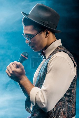 side view of male singer performing with microphone on stage with smoke and dramatic lighting