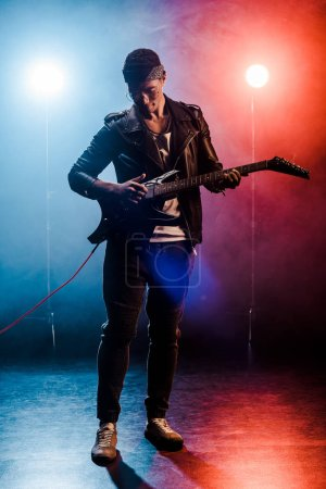 concentrated male rock star in leather jacket performing on electric guitar on stage with smoke and dramatic lighting