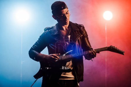 male musician playing on electric guitar on stage with smoke and dramatic lighting