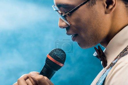 Foto de Vista parcial del hombre de raza mixta, cantar en el micrófono en el escenario con iluminación humo y dramática - Imagen libre de derechos