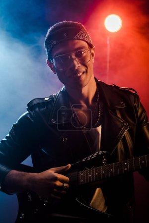 Foto de Músico masculino alegre en chaqueta de cuero tocando en la guitarra eléctrica en el escenario con iluminación humo y dramática - Imagen libre de derechos