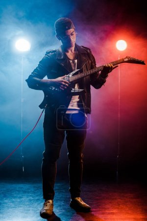 Photo for Concentrated man in leather jacket performing on electric guitar on stage with smoke and dramatic lighting - Royalty Free Image