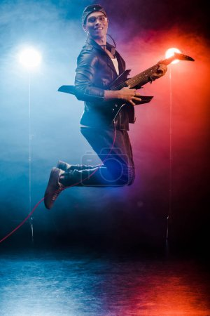 happy male musician jumping and performing on electric guitar during rock concert on stage with smoke and spotlights