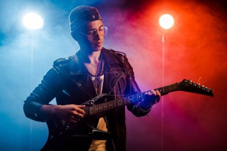 focused male musician in leather jacket performing on electric guitar on stage with smoke and dramatic lighting