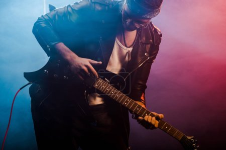 young male rocker in leather jacket performing on electric guitar on stage with smoke and dramatic lighting