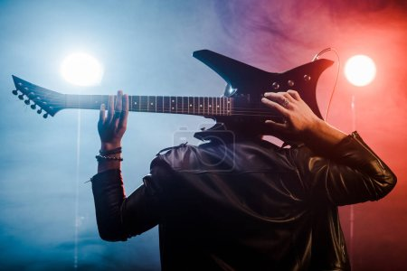 Photo for Rear view of male musician in leather jacket playing on electric guitar behind head on stage - Royalty Free Image