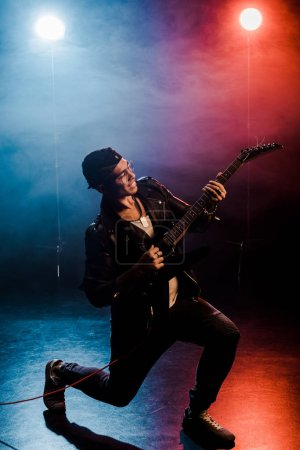 smiling male rock star in leather jacket performing on electric guitar on stage with smoke and dramatic lighting