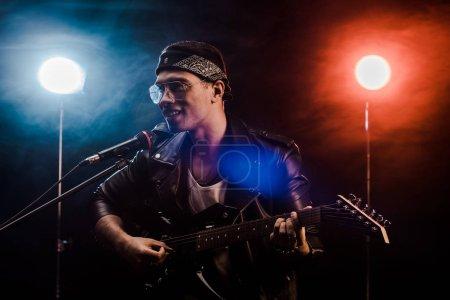 Photo pour Souriant musicien mâle chantant dans le microphone et jouer à la guitare électrique sur scène pendant le concert de rock - image libre de droit