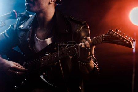 Photo pour Vue partielle du jeune homme chantant dans le microphone et jouer à la guitare électrique sur scène pendant le concert de rock - image libre de droit