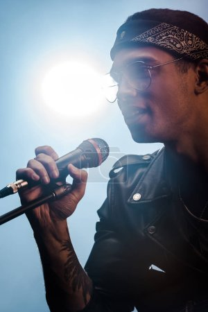 Photo for Handsome male rock musician singing in microphone on stage with spotlight - Royalty Free Image