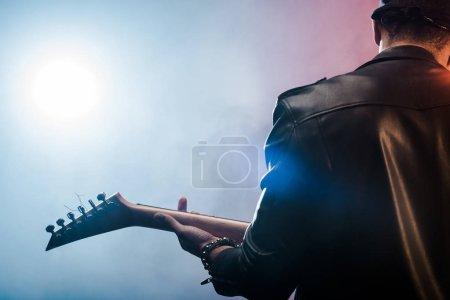 Photo for Rear view of male rock star in leather jacket performing on electric guitar on stage with smoke and dramatic lighting - Royalty Free Image