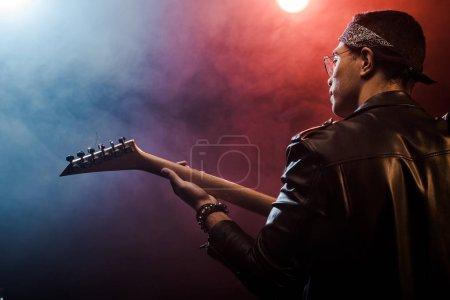 Photo pour Vue arrière du musicien mâle en blouson de cuir, jouant à la guitare électrique sur scène avec un éclairage fumée et dramatique - image libre de droit