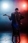 "Постер, картина, фотообои ""вид сзади мужчин рокер, сидя на стуле и играл на электрической гитаре на сцене во время концерта"""