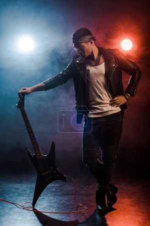 Photo for Young mixed race rock musician in leather jacket posing with electric guitar on stage with smoke and dramatic lighting - Royalty Free Image