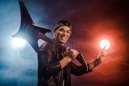 Foto de Macho rockero en chaqueta de cuero posando con la guitarra eléctrica y hacer señal de cuernos sobre el escenario con humo y espectacular iluminación - Imagen libre de derechos