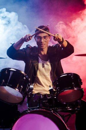 Photo for Happy mixed race male musician raising drum sticks while sitting behind drum set on stage with dramatic lighting and smoke - Royalty Free Image