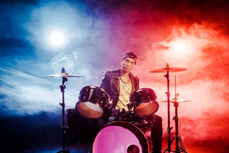 confident mixed race male musician sitting behind drum set on stage with spotlights