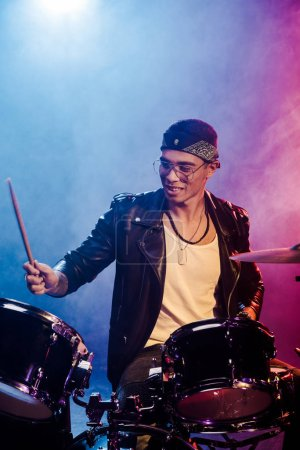 joyful young male musician in leather jacket playing drums during rock concert on stage with smoke and dramatic lighting