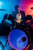 """Постер, картина, фотообои """"красивый мужской музыкант в кожаной куртке, играть на барабанах во время рок-концерт на сцене с дымом и драматическое освещение"""""""