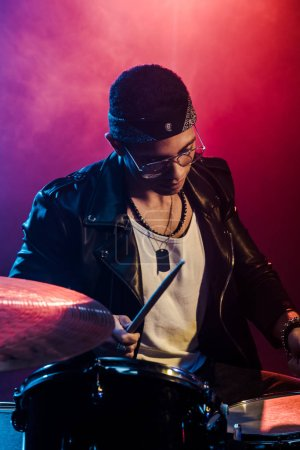 serious young male musician in leather jacket playing drums during rock concert on stage with smoke and dramatic lighting