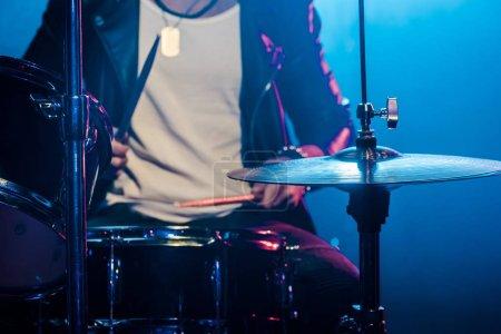 Photo pour Cropped image des tambours jouant musicien mâle pendant le concert de rock sur scène avec un éclairage fumée et dramatique - image libre de droit